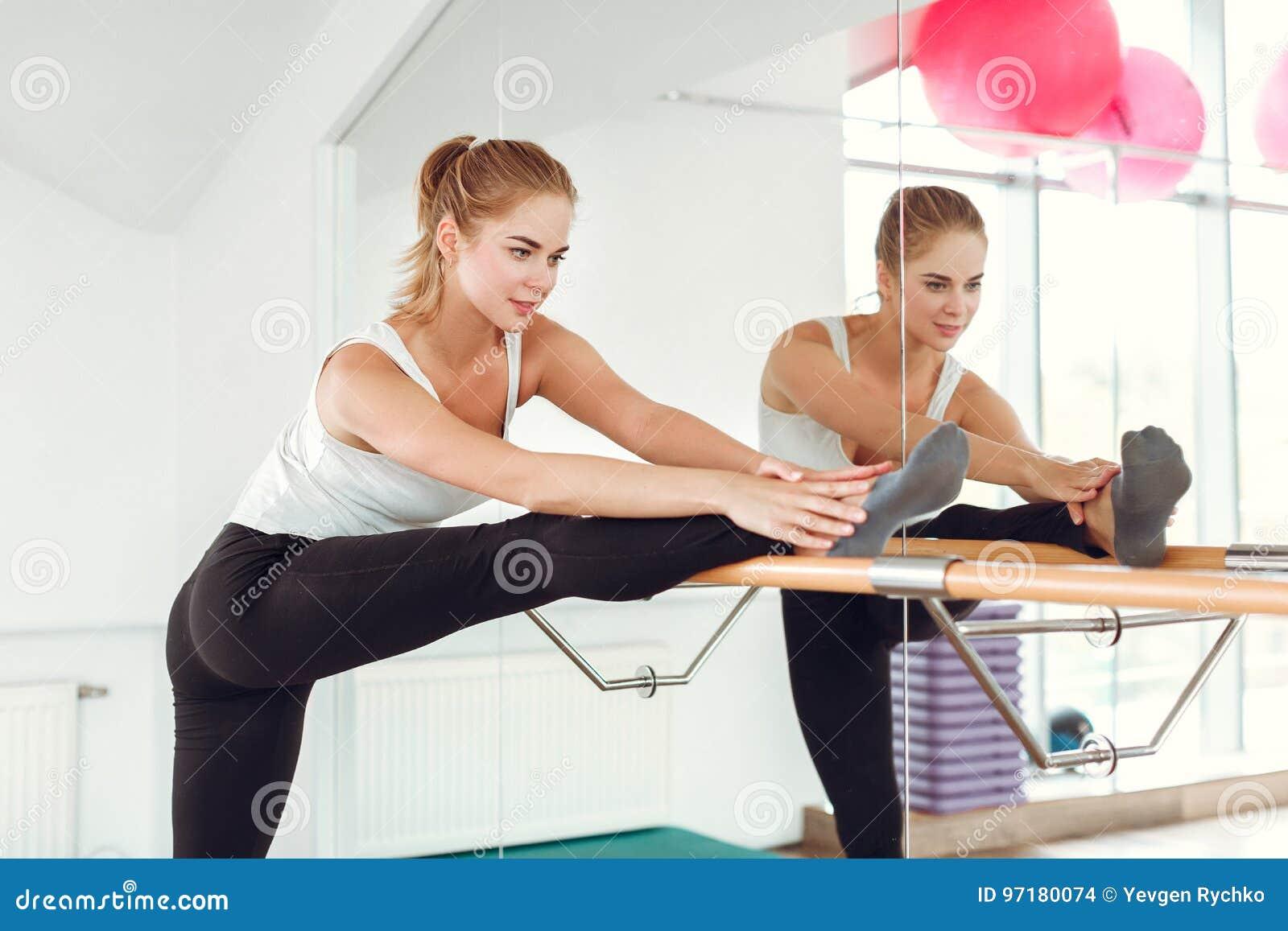 Mulher delgada bonita no sportswear que estica perto da barra do bailado