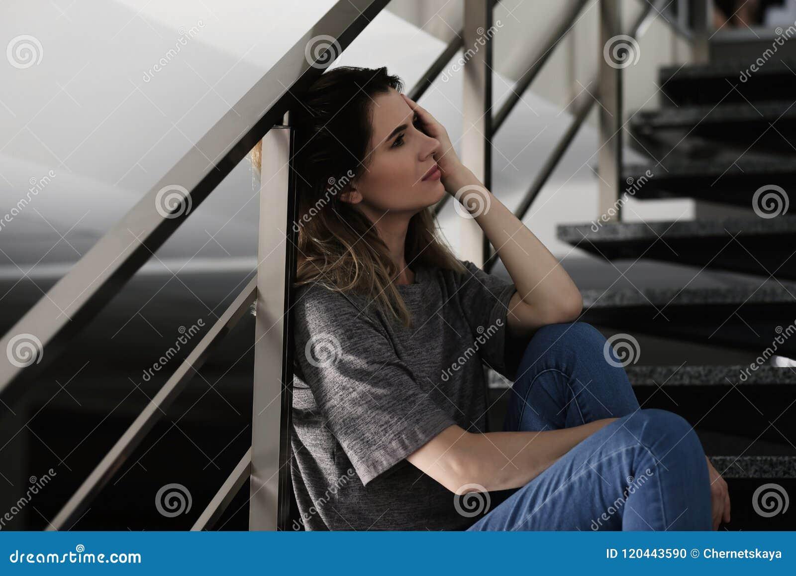 Mulher deprimida só que senta-se em escadas