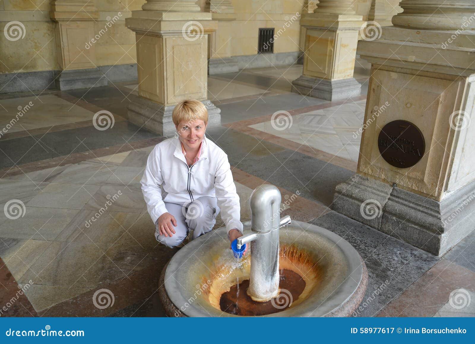 A mulher derrama a água de uma fonte mineral em Karlovy varia