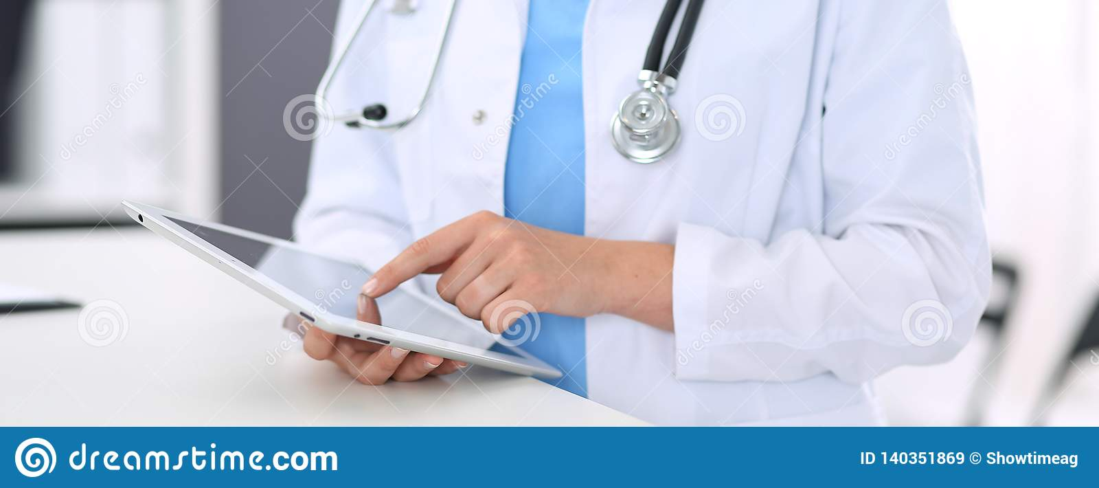 Mulher desconhecida do doutor no trabalho Médico fêmea que usa a tabuleta digital ao estar perto da mesa de recepção na clínica o