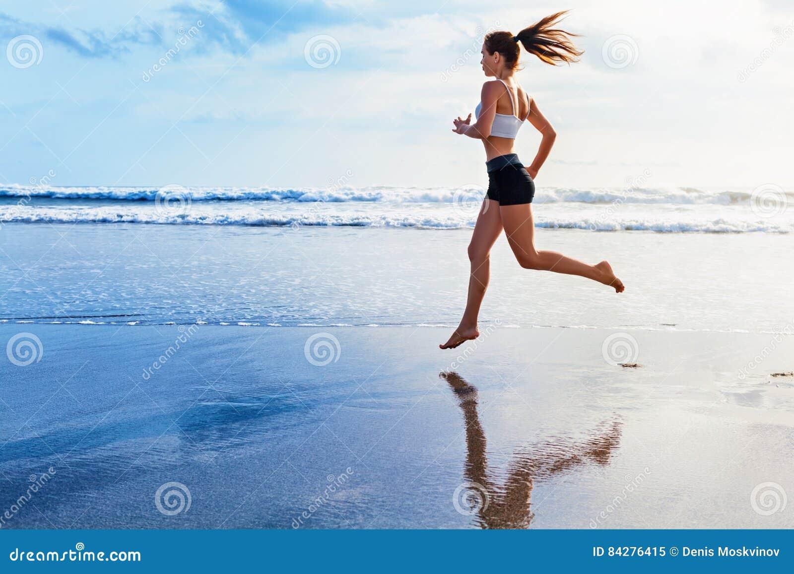 A mulher desportiva ativa corre ao longo da praia do oceano do por do sol Ostenta o fundo