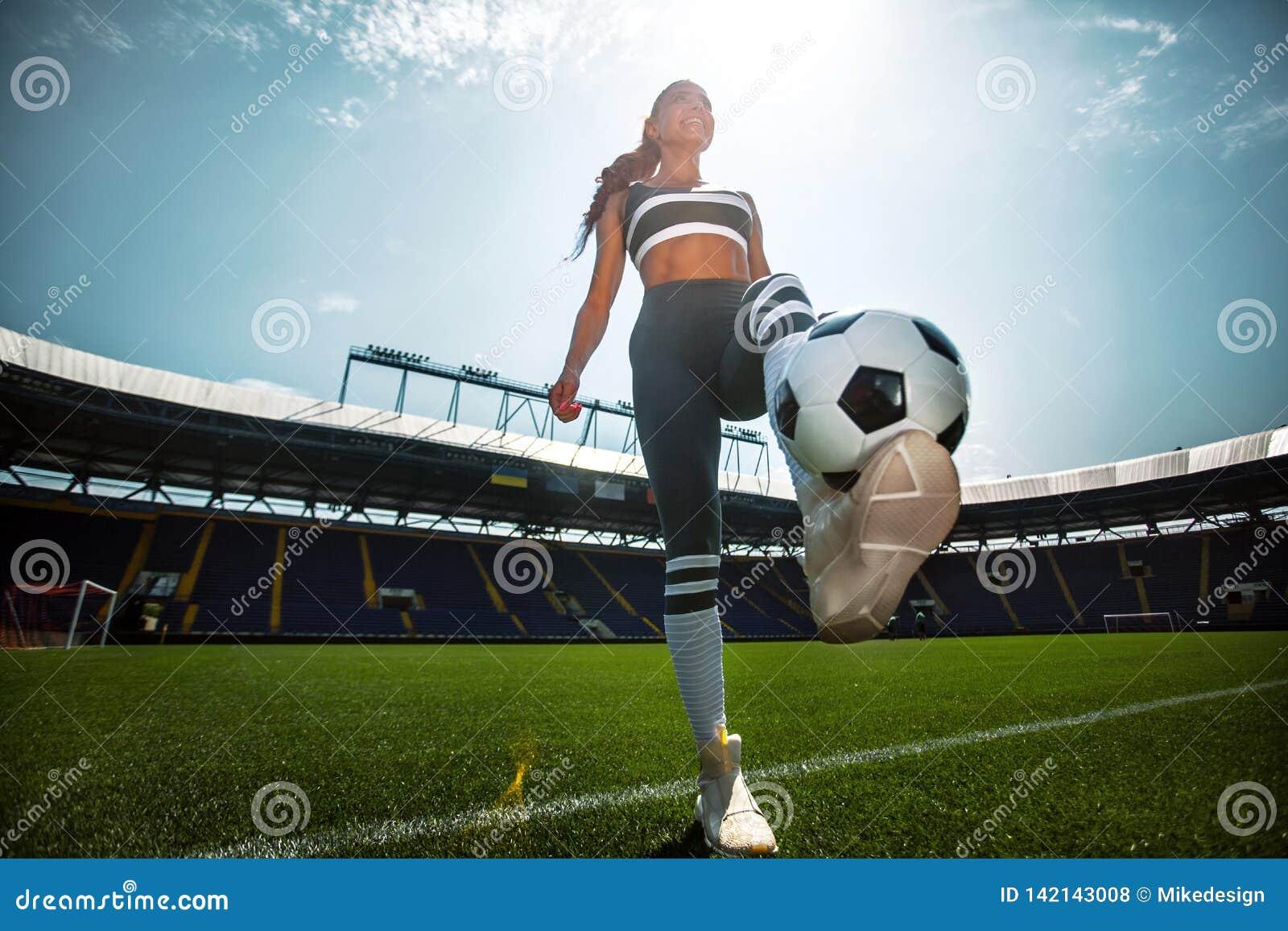 Mulher desportiva atlética no sportswear com a bola de futebol no estádio