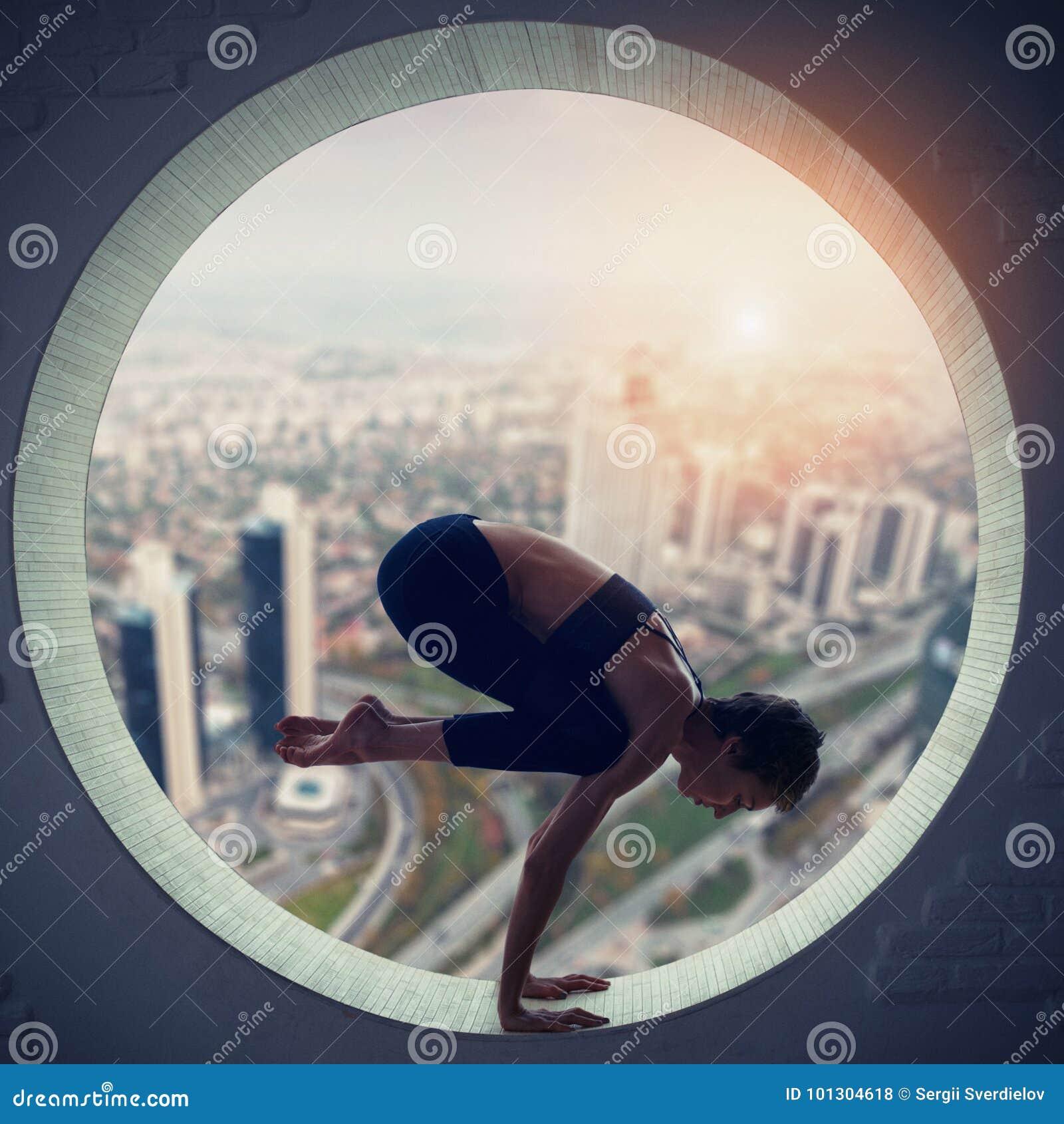 A mulher desportiva bonita do iogue do ajuste pratica o asana Bakasana da ioga - crane a pose em uma janela redonda