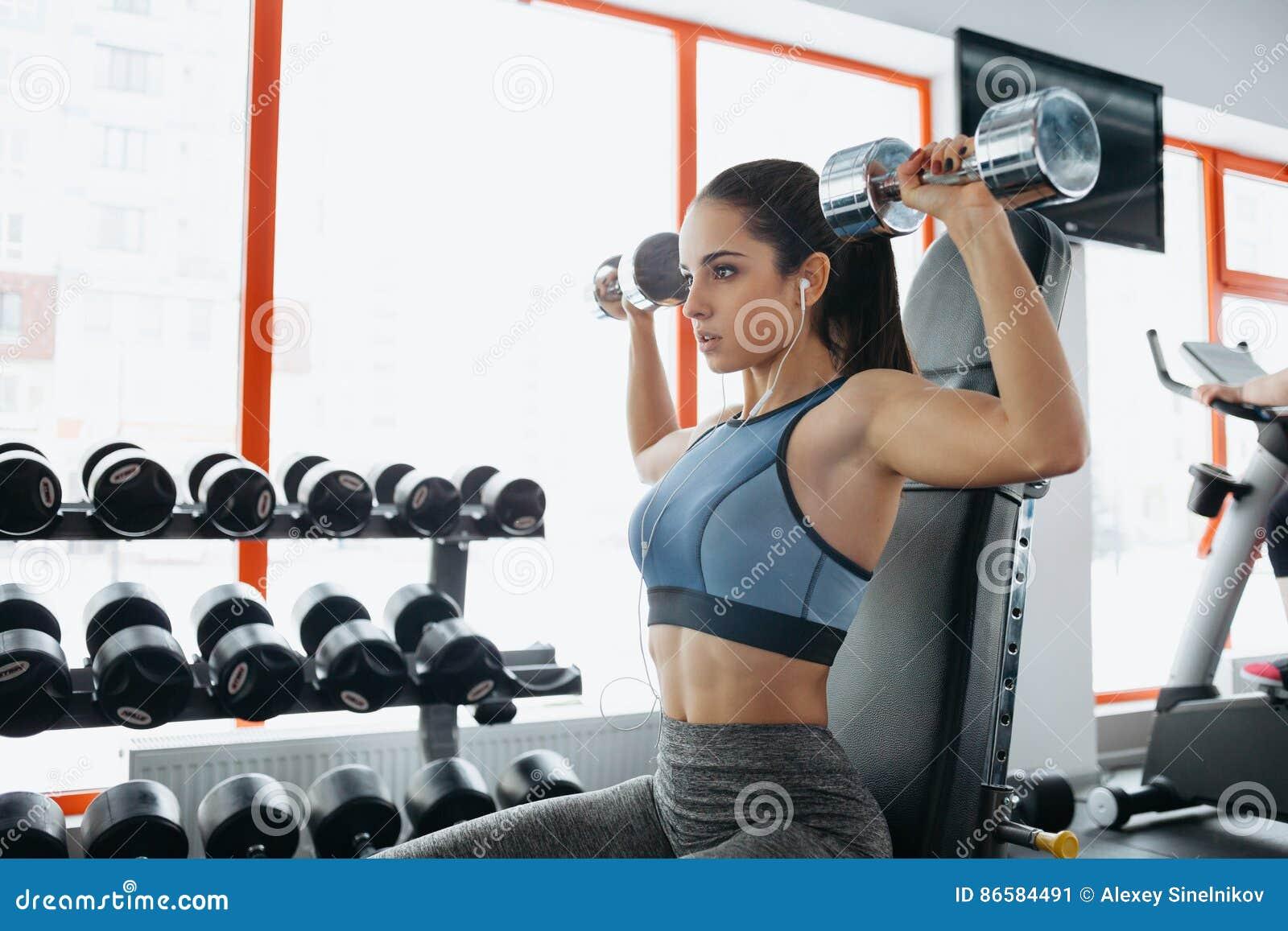 Mulher desportiva bonita que faz o exercício da aptidão do poder no gym do esporte