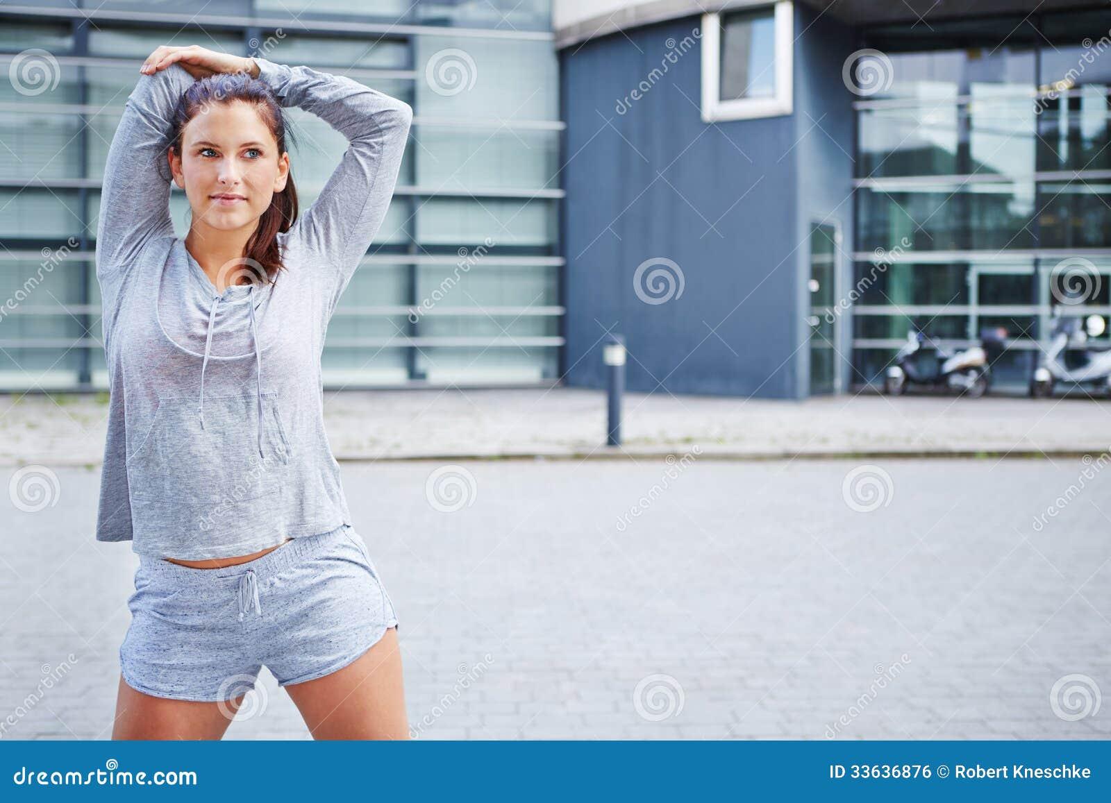 Mulher desportiva que aquece-se antes de correr
