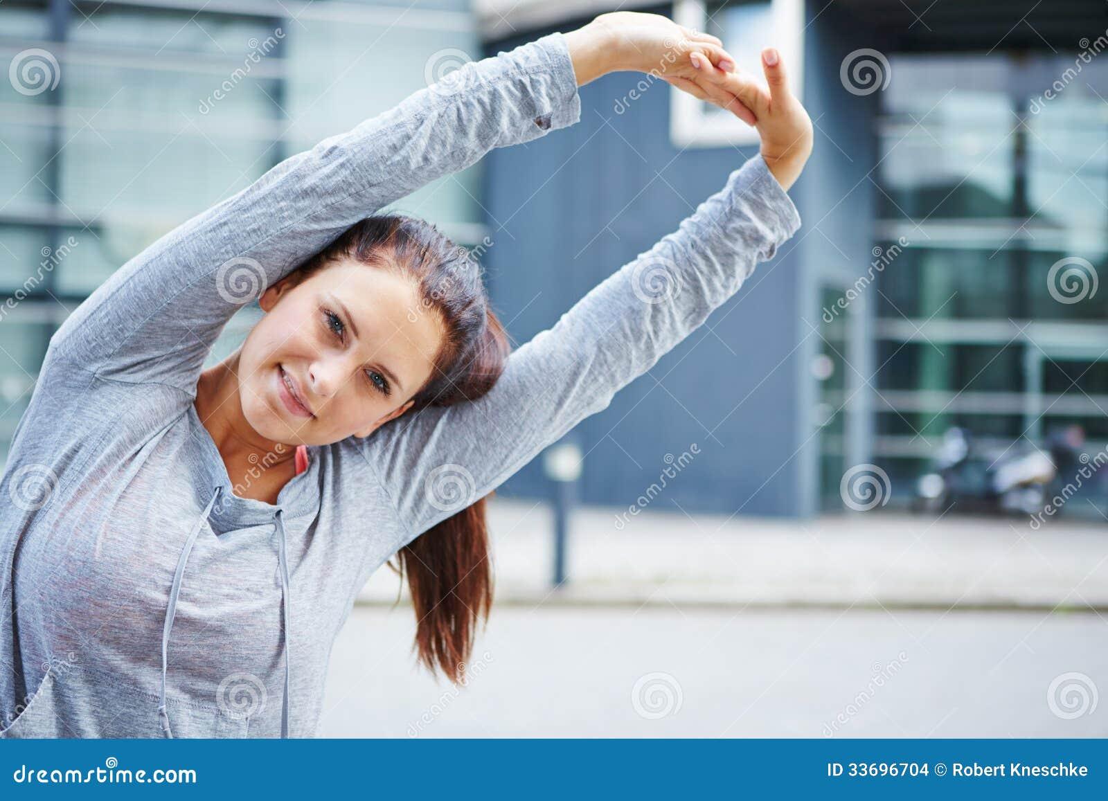 Mulher desportiva que faz esticando o exercício