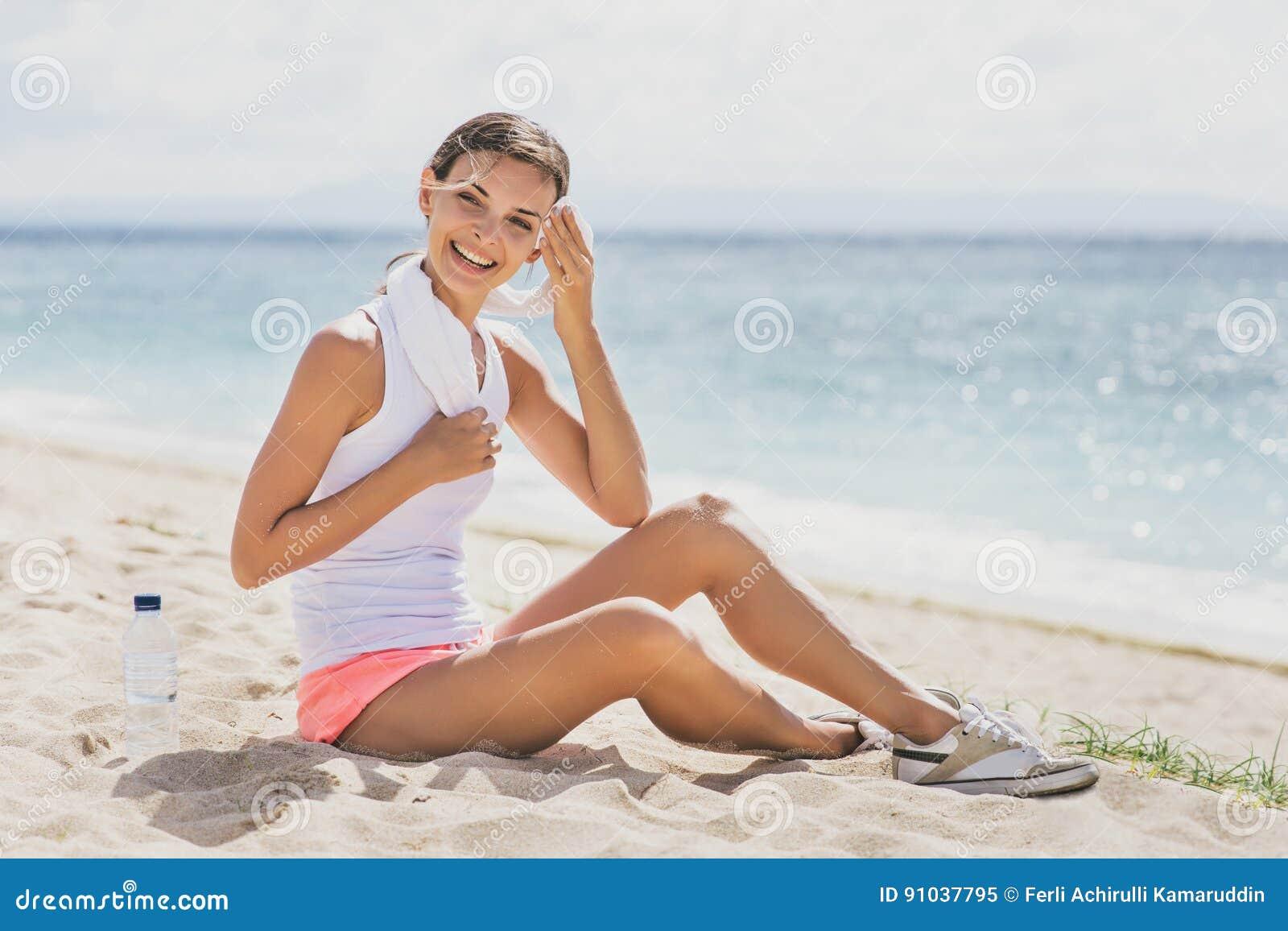 Mulher desportiva que sorri ao descansar após o exercício