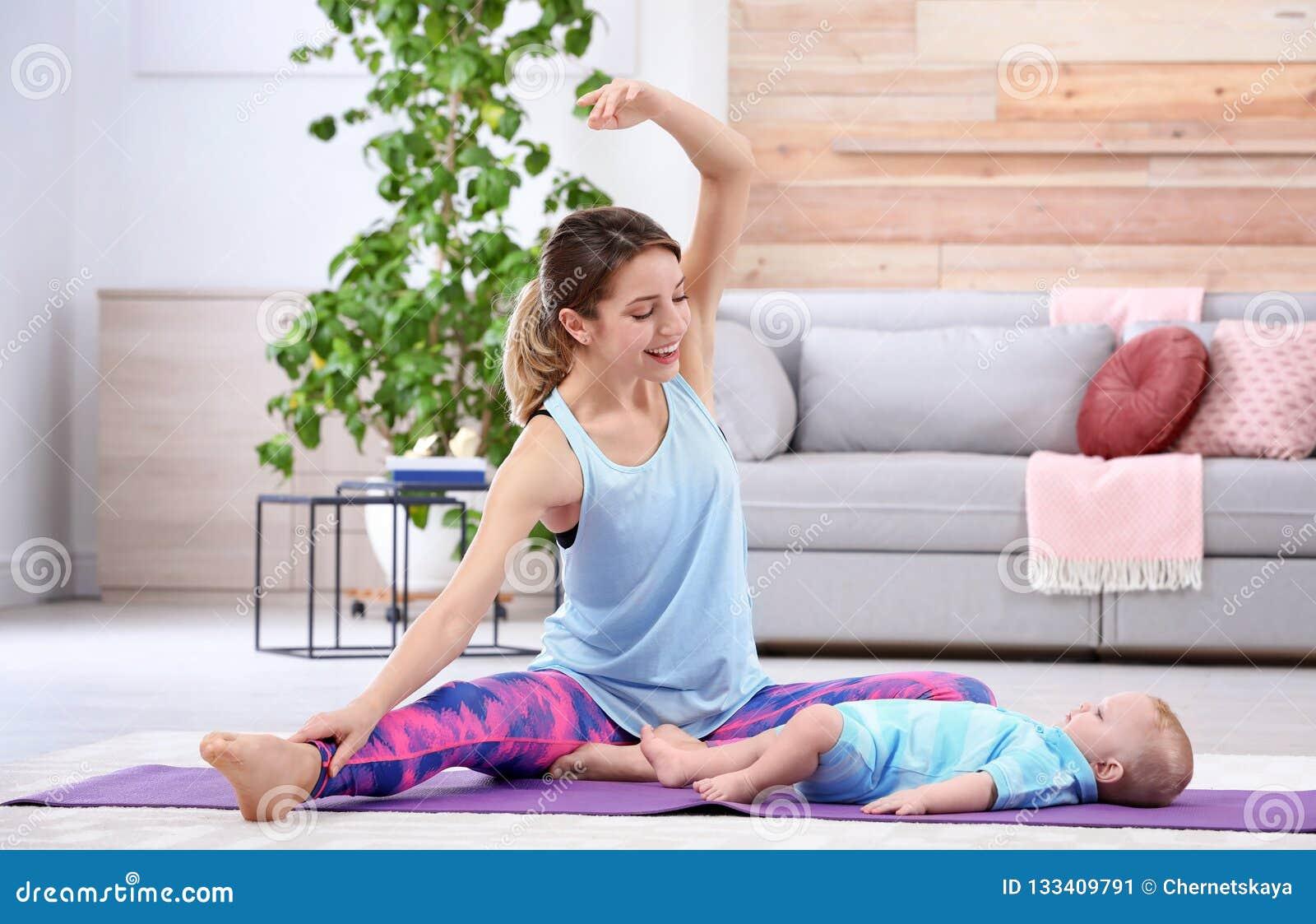 Mulher desportivo nova que faz o exercício com seu filho em casa