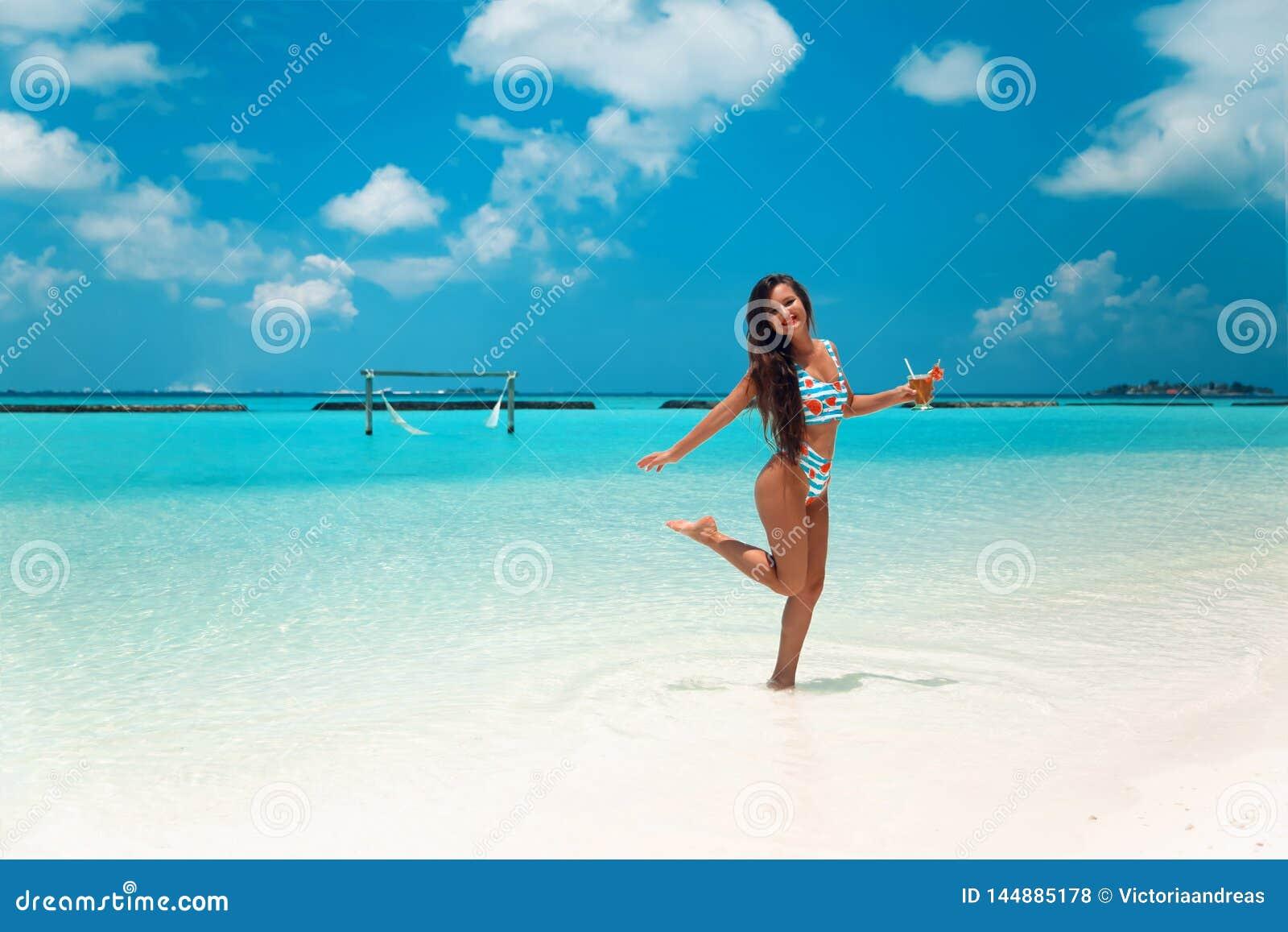 Mulher despreocupada do biquini na praia tropical Menina magro bonita com coctail que aprecia na ilha exótica no oceano de turqu