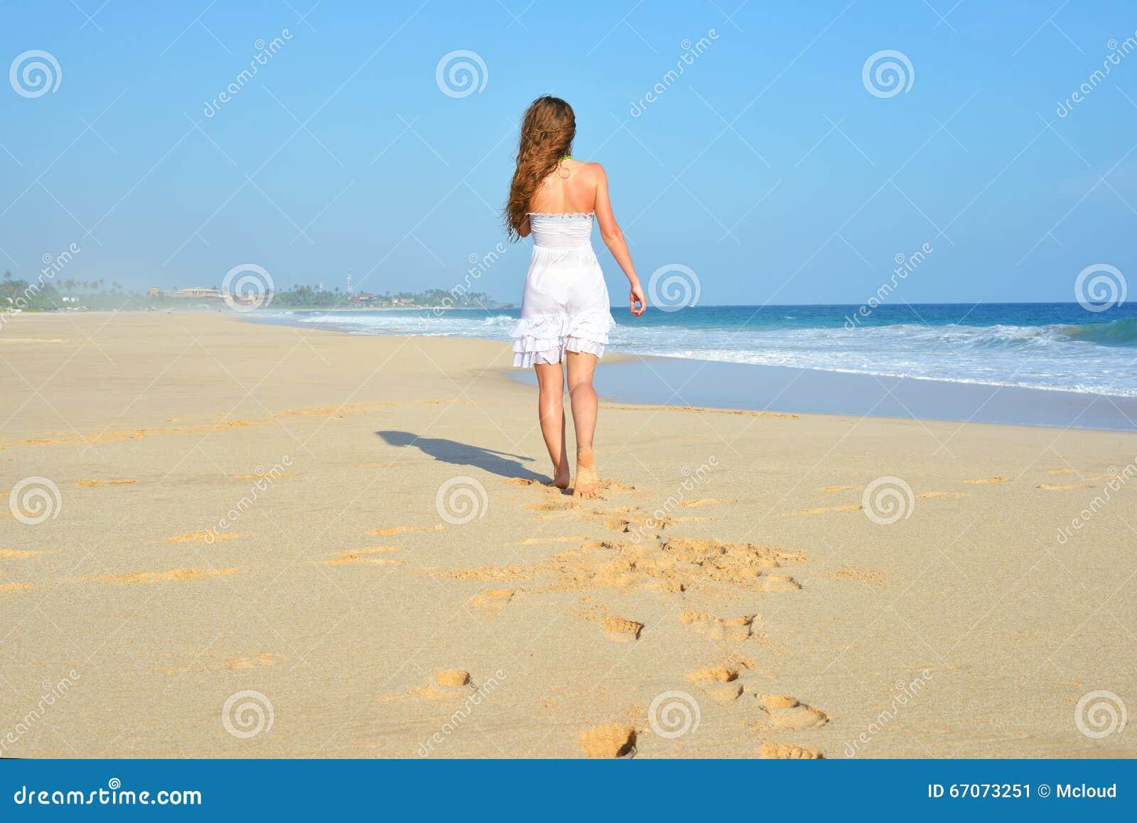 Mulher despreocupada feliz que anda na praia que comemora sua liberdade Fundo da mulher do verão do oceano e da areia Opinião tra