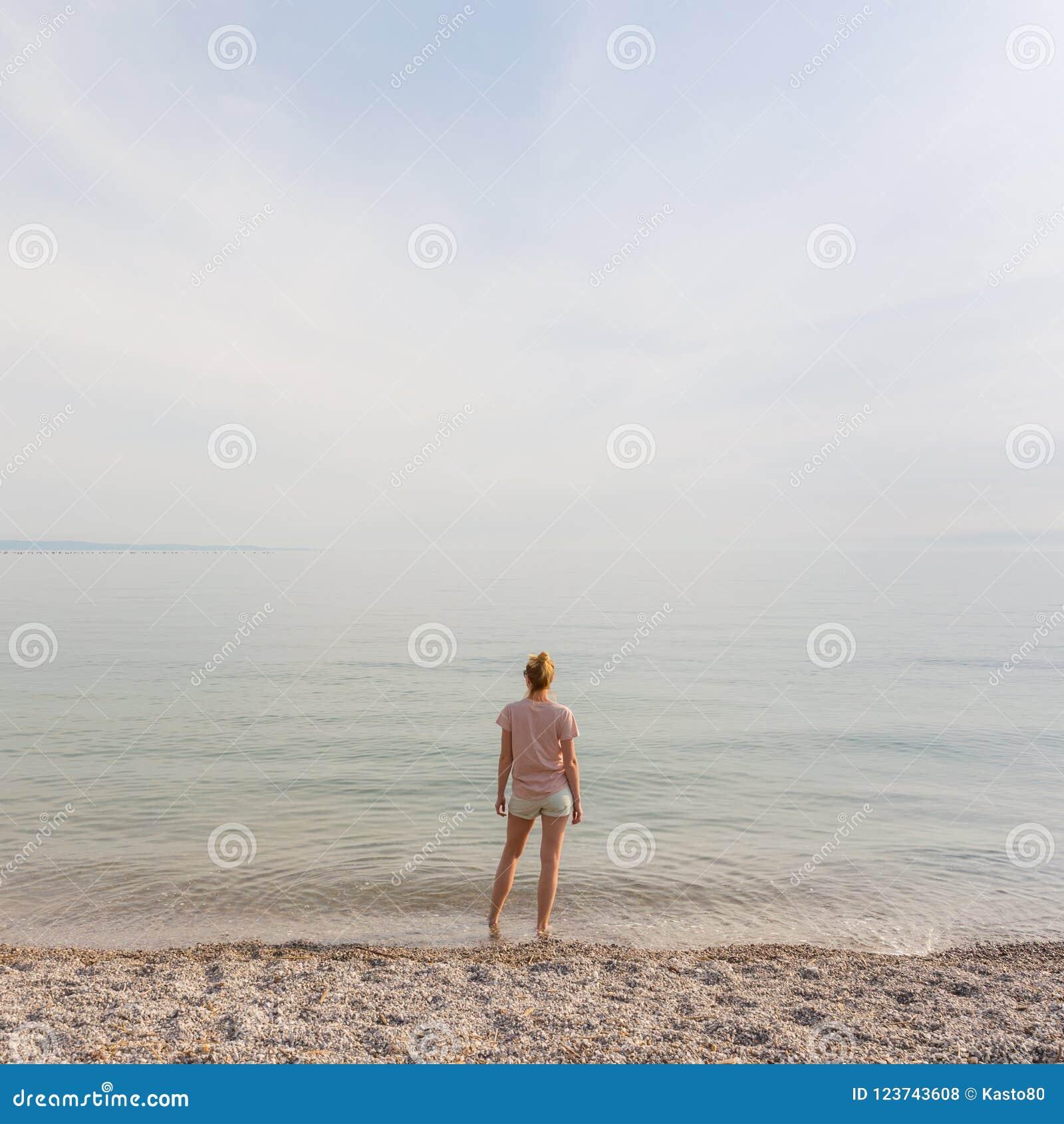 Mulher despreocupada feliz que aprecia a caminhada do por do sol na praia branca de Pabbled
