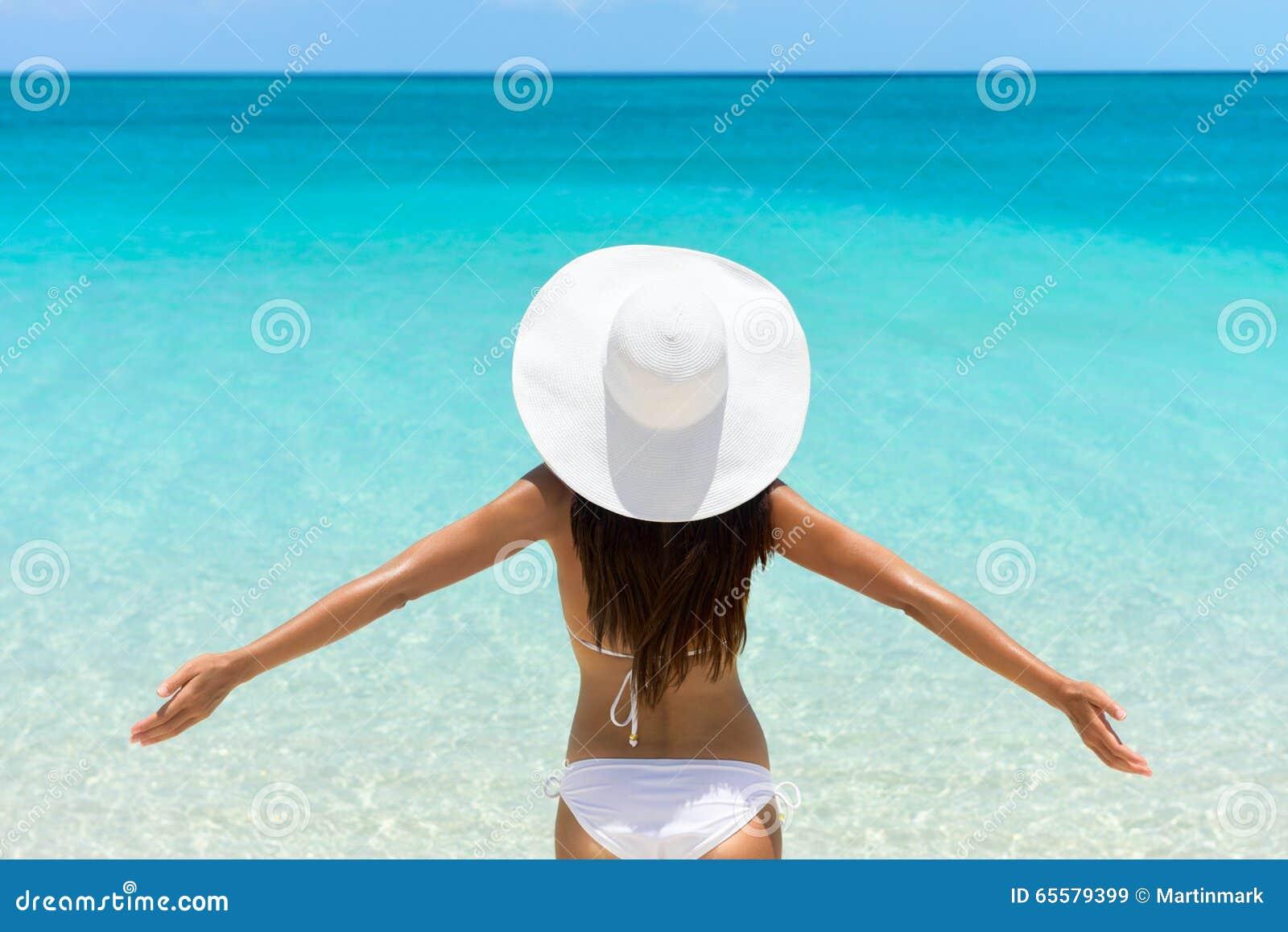 Mulher despreocupada na praia no chapéu e no biquini brancos