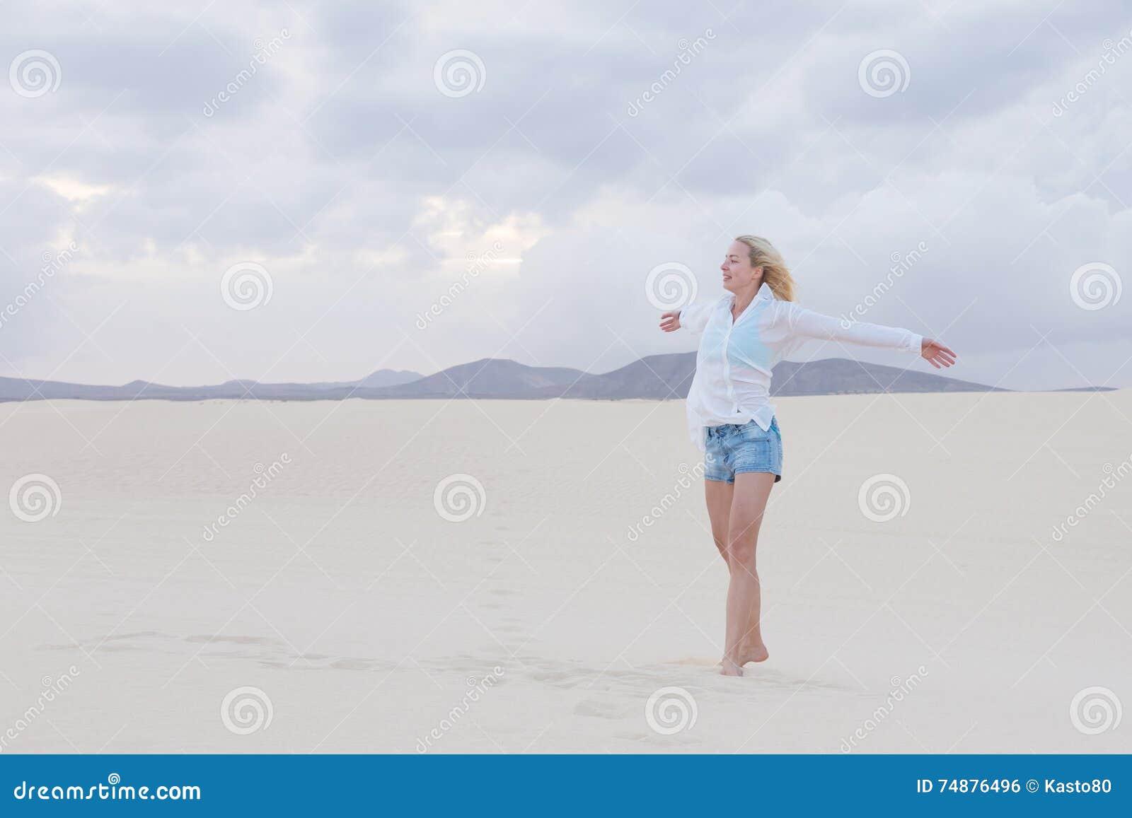 Mulher despreocupada que aprecia a liberdade na praia