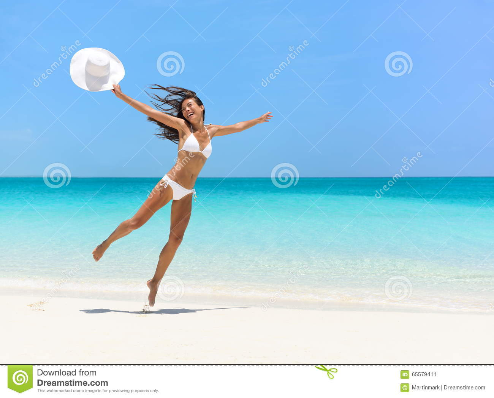Mulher despreocupada que salta na praia durante o verão