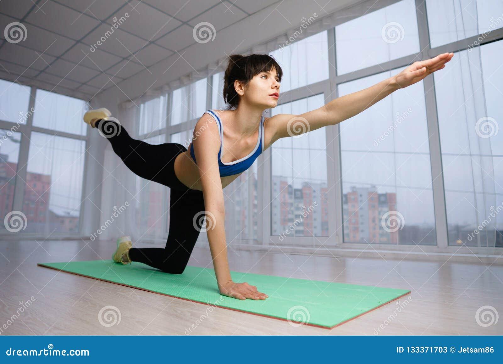 Mulher do ajuste que faz o exercício isométrico durante o exercício