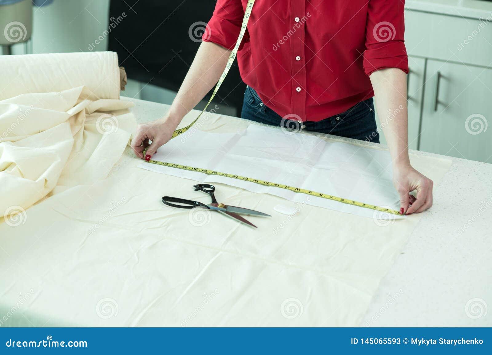Mulher do alfaiate que mede uma parte de pano de matéria têxtil na oficina
