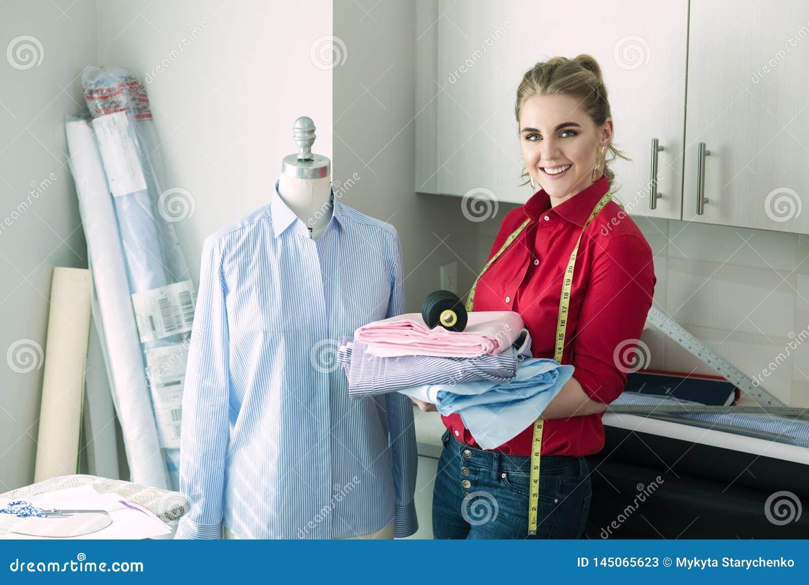 Mulher do alfaiate que sorri no estúdio do projeto da oficina que guarda costurar ferramentas