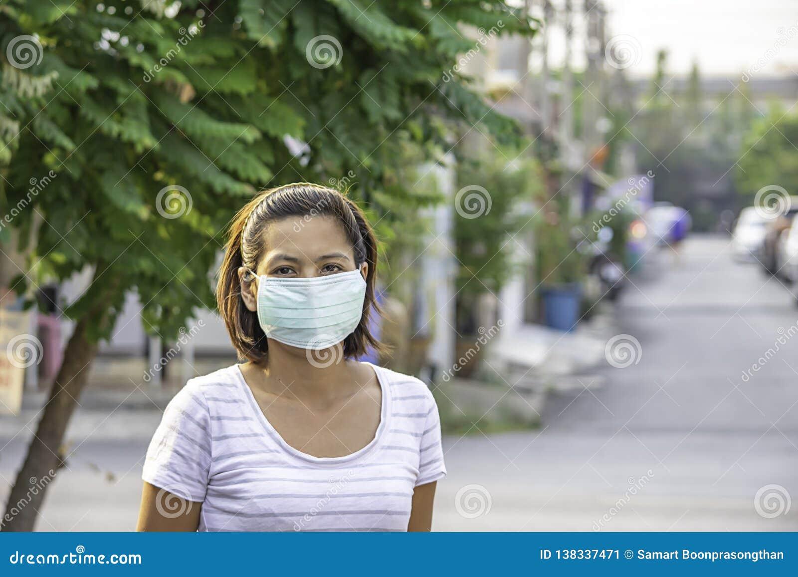A mulher do Asean veste uma máscara para impedir a poeira em Banguecoque, Tailândia