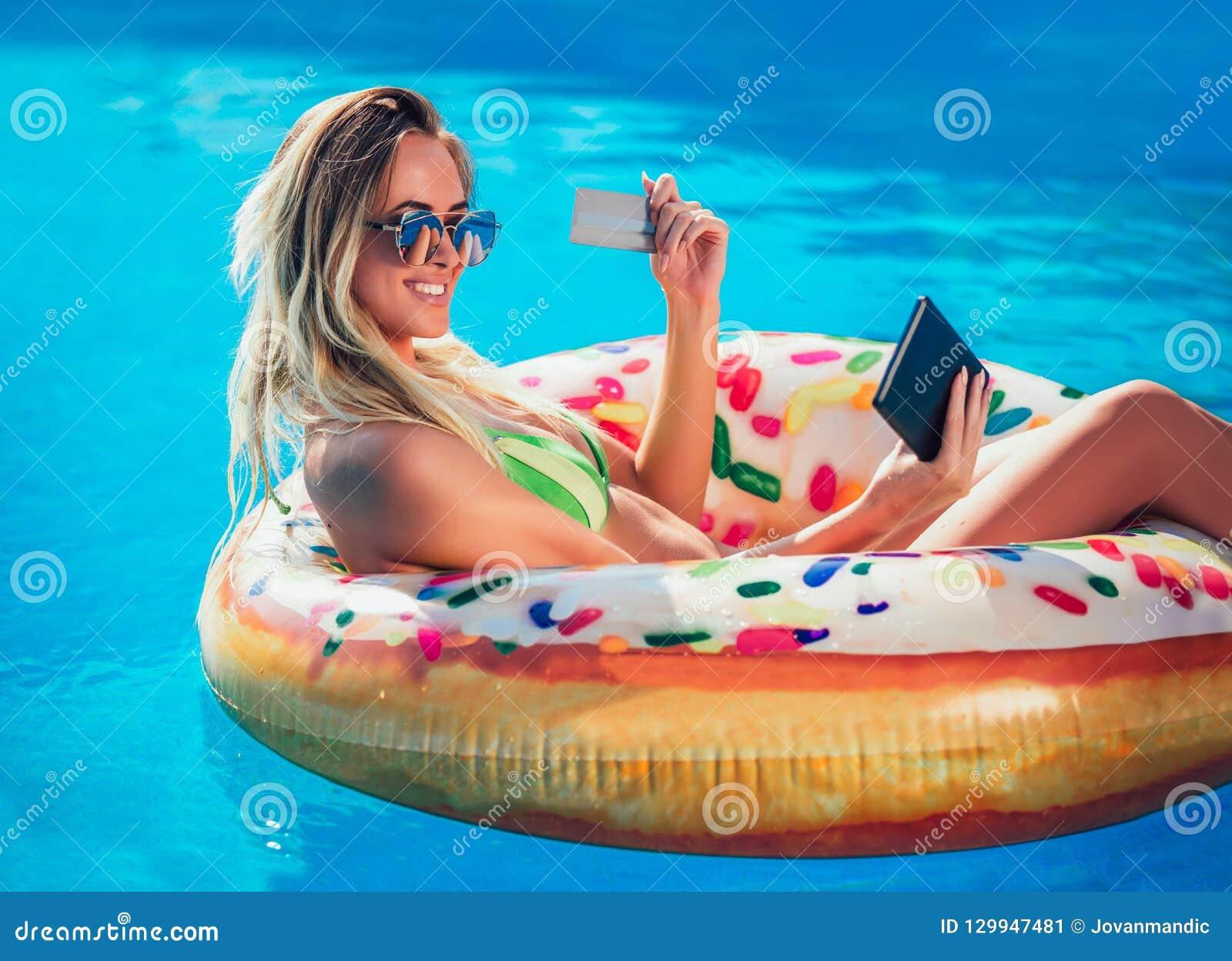 Mulher do bronzeado de Njoying no biquini no colchão inflável na piscina que usa o cartão digital da tabuleta e de crédito