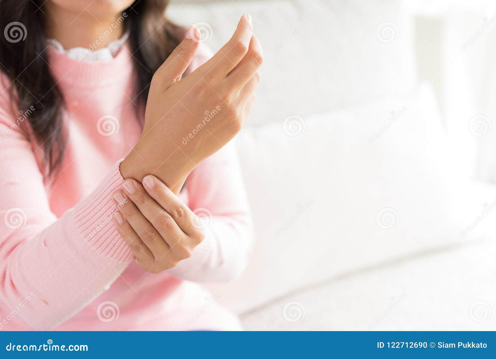 A mulher do close up que senta-se no sofá guarda seu ferimento de mão do pulso