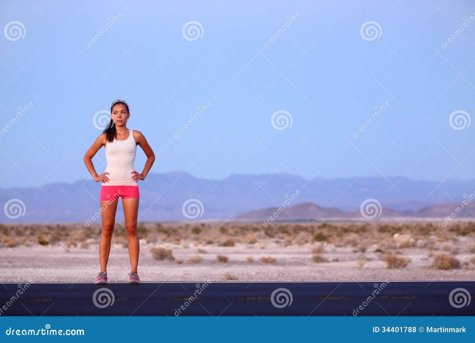 Mulher do corredor do atleta que descansa na estrada após a corrida