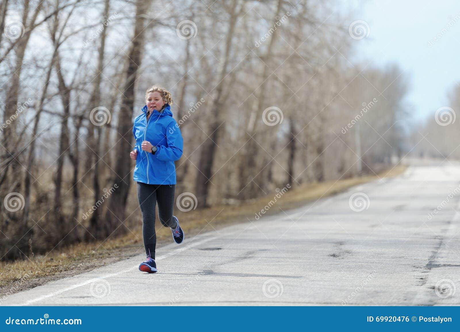 Mulher do corredor que corre na estrada na natureza bonita Traini movimentando-se