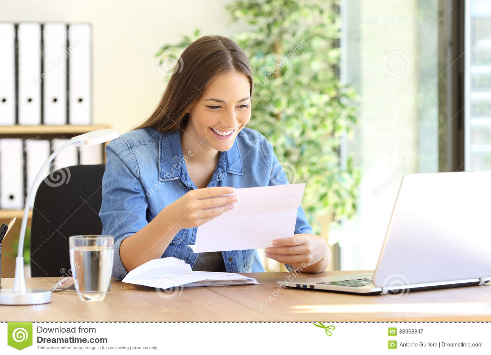 Mulher do empresário que lê uma letra no escritório
