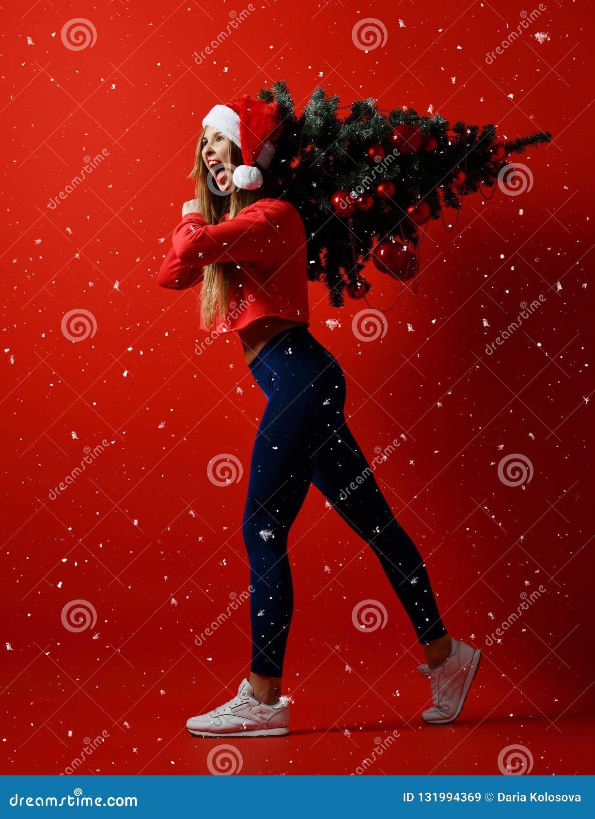 Mulher do esporte da aptidão do Natal que veste o chapéu de Santa que guarda a árvore do xmas em seus ombros Flocos de neve