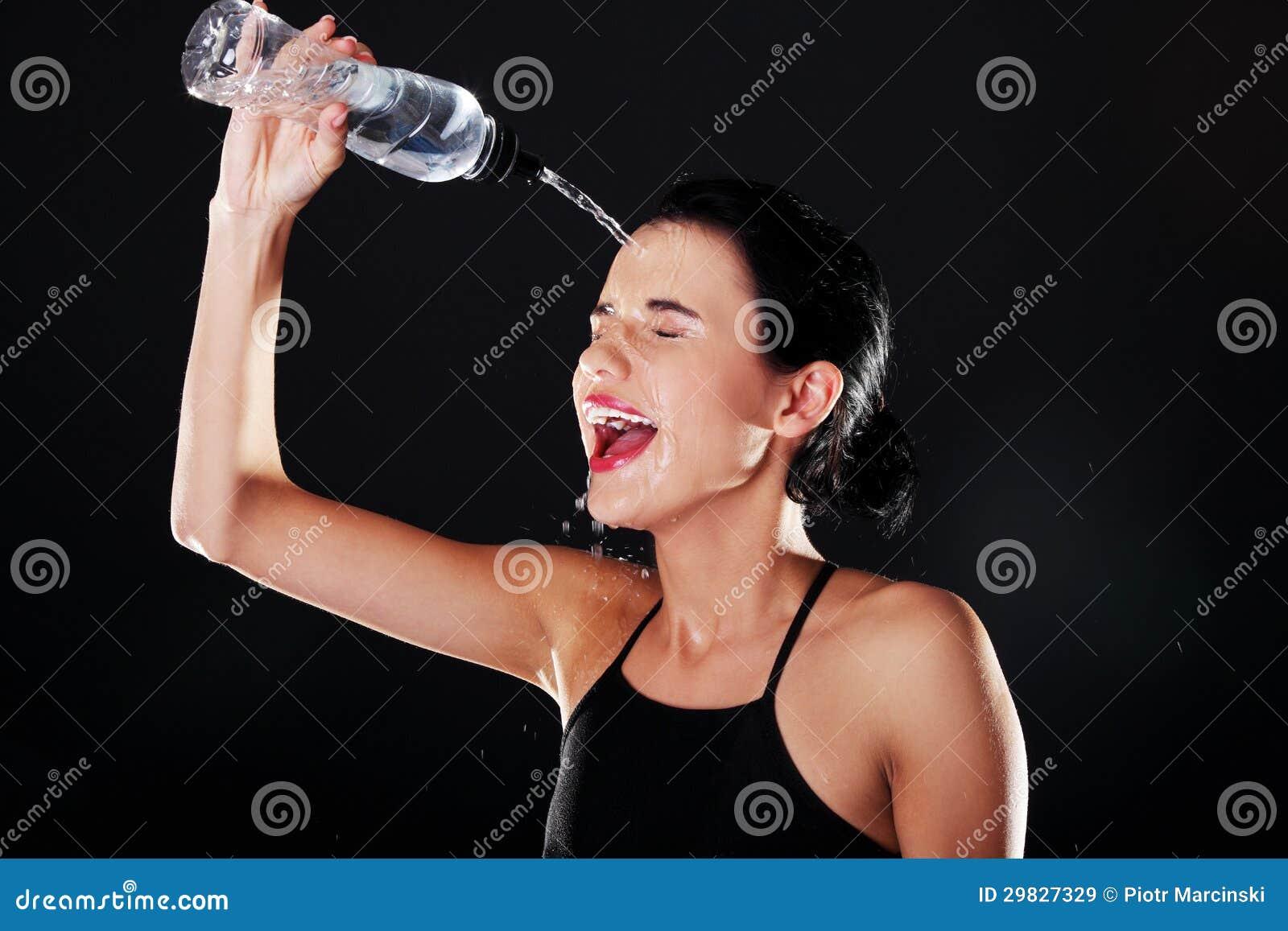 Mulher do esporte que refrigera-se com água