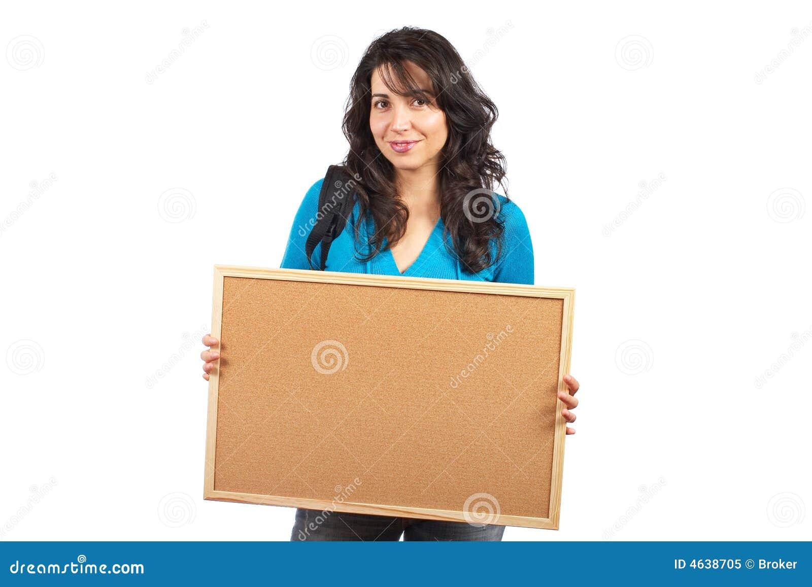 Mulher do estudante que prende o corkboard vazio