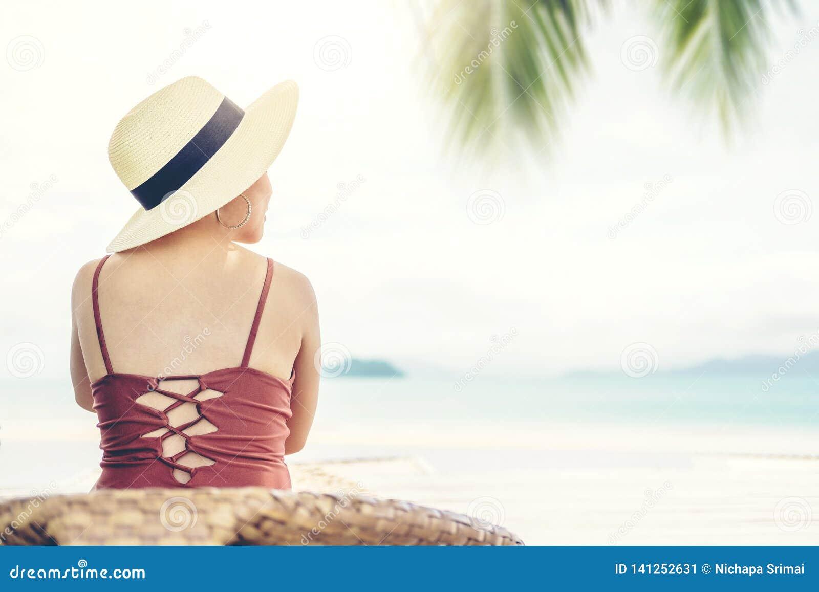 Mulher do feriado da praia do verão para relaxar na praia no tempo livre