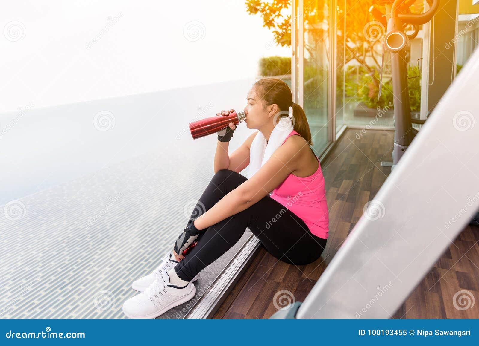 Mulher do Gym que dá certo a água potável de assento no fitness center