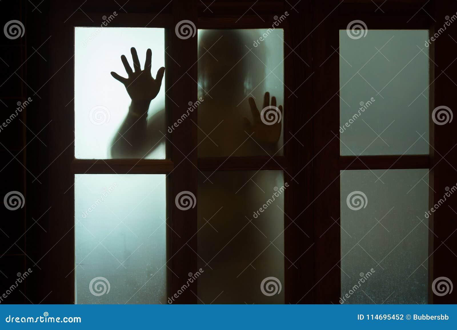 Mulher do horror atrás do vidro de janela em preto e branco blurry