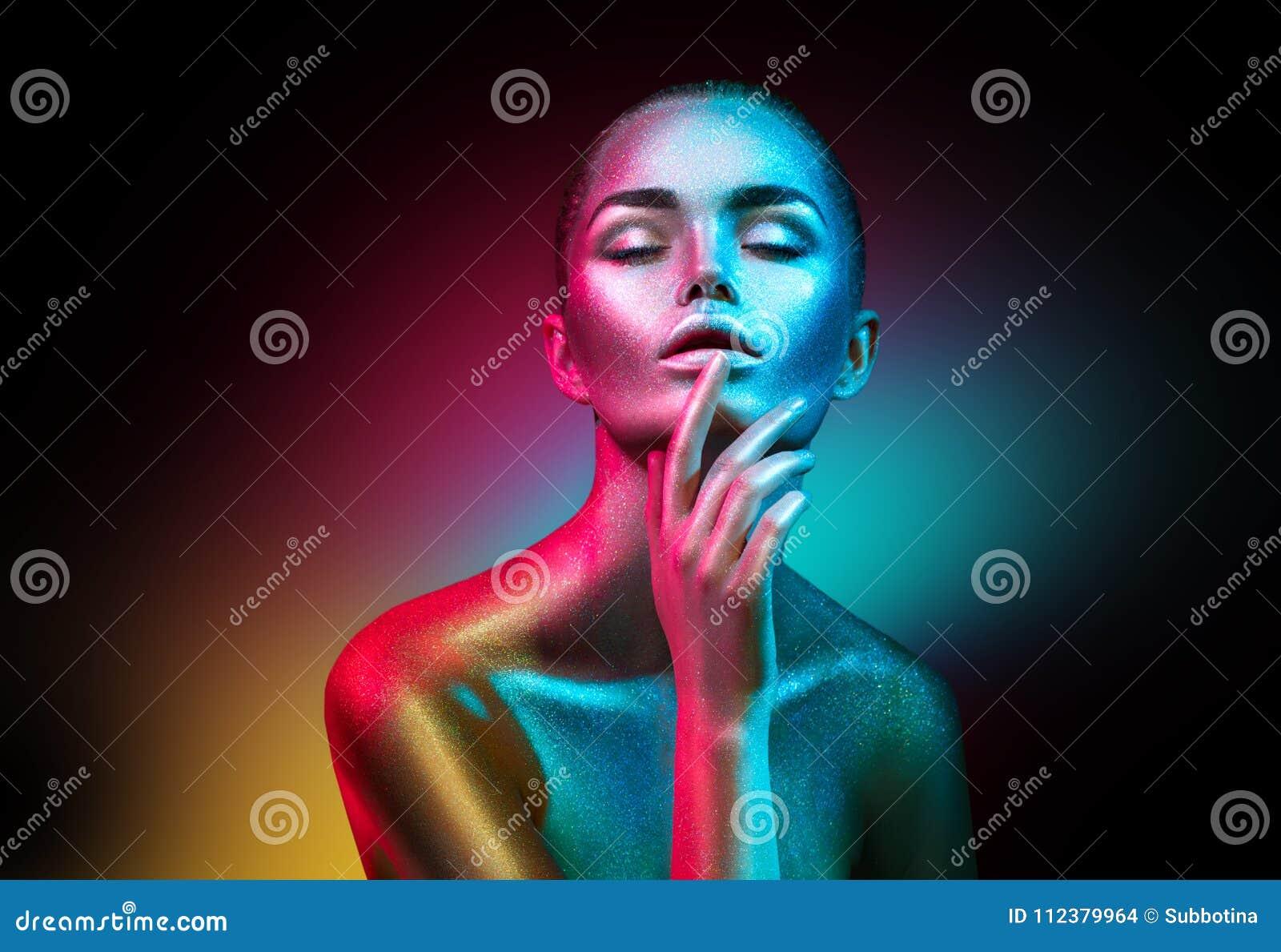 Mulher do modelo de forma em sparkles brilhantes coloridos e nas luzes de néon que levantam no estúdio, retrato da menina  sexy