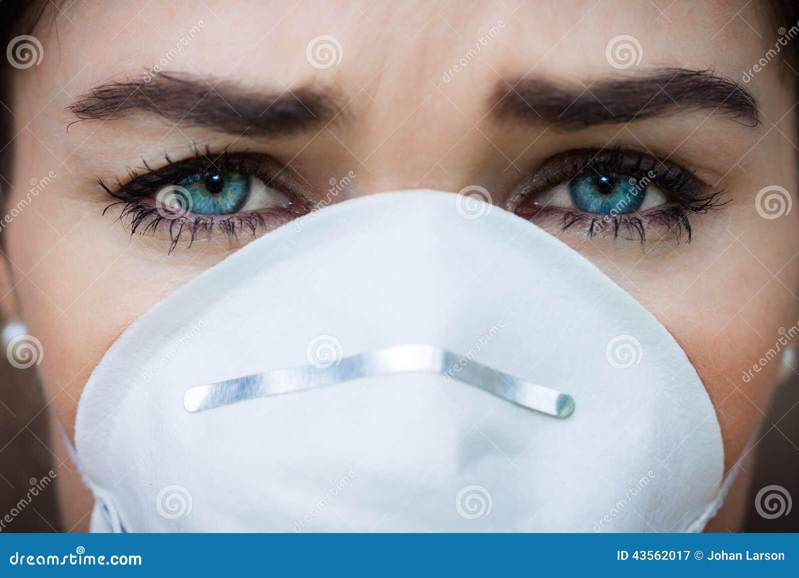Mulher do retrato do close-up que veste uma máscara protetora