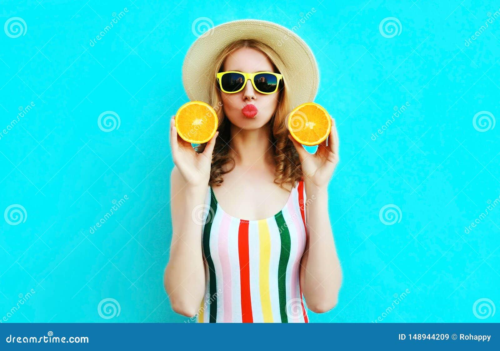 Mulher do retrato do ver?o que realiza em suas m?os duas fatias de fruto alaranjado no chap?u de palha no azul colorido