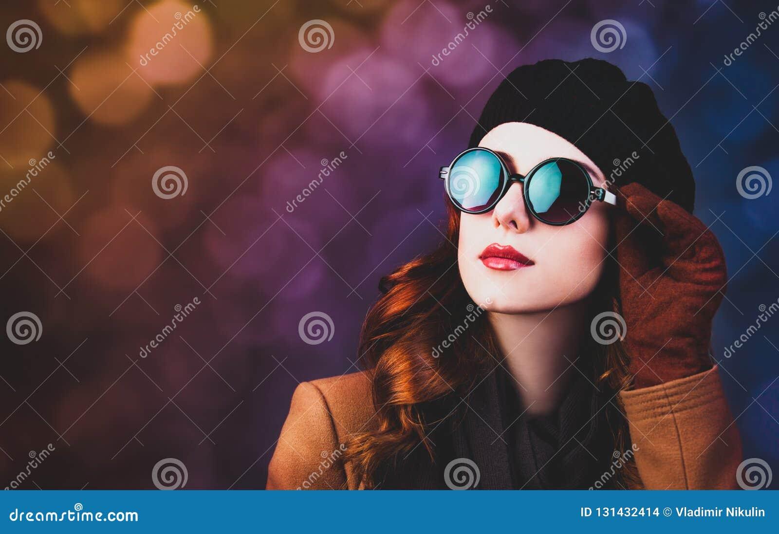 Mulher do ruivo do estilo nos óculos de sol e no revestimento