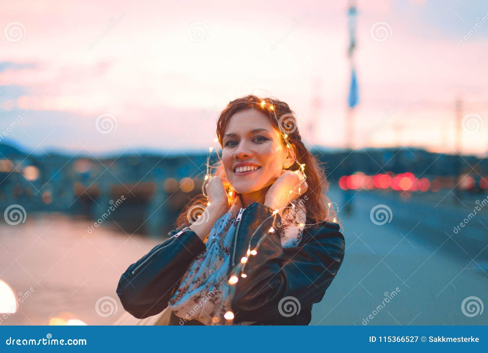 Mulher do ruivo que joga com luzes feericamente fora, cerceta e orangotango