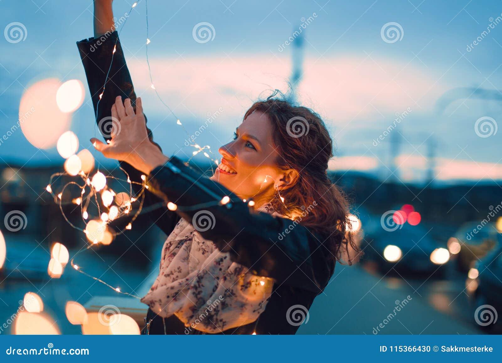 Mulher do ruivo que joga com luzes feericamente fora e sorriso no ev