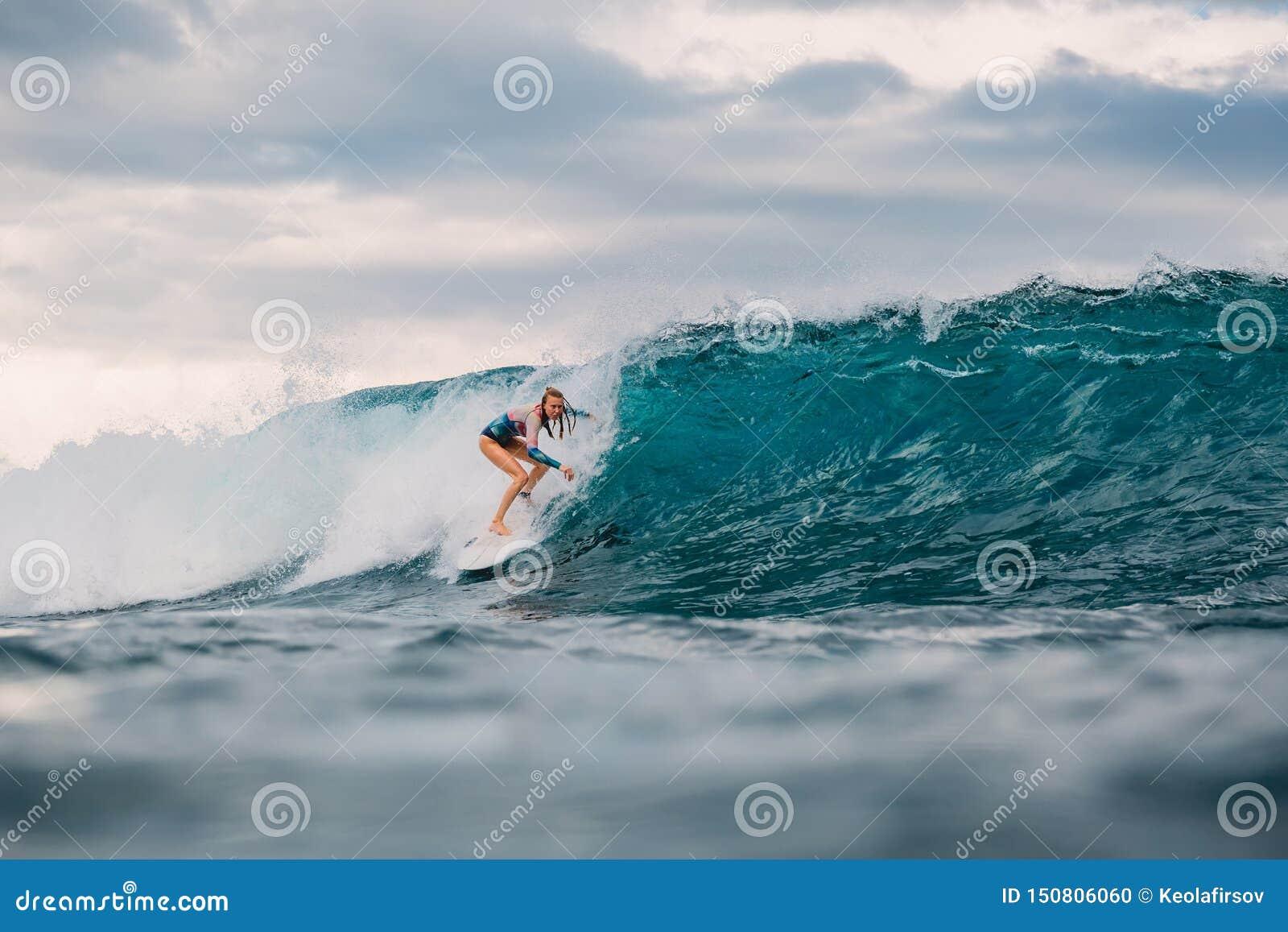 Mulher do surfista e onda azul grande