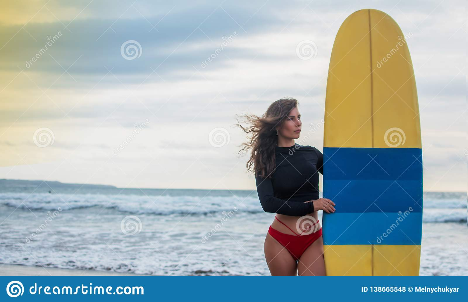 Mulher do surfista que vai surfando a posição com a prancha azul-amarela na praia de Waikiki Menina fêmea do biquini que anda com