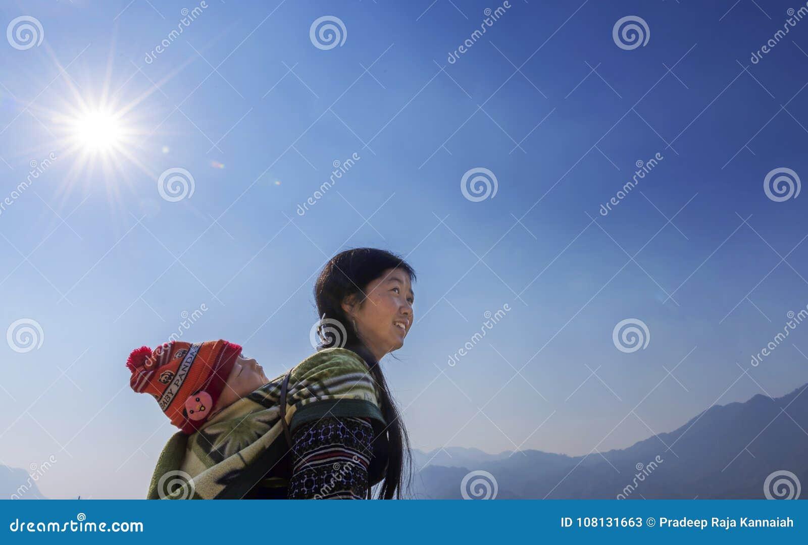 Mulher do tribo de Hmong que leva sua criança nela para trás em Sapa, Vietname