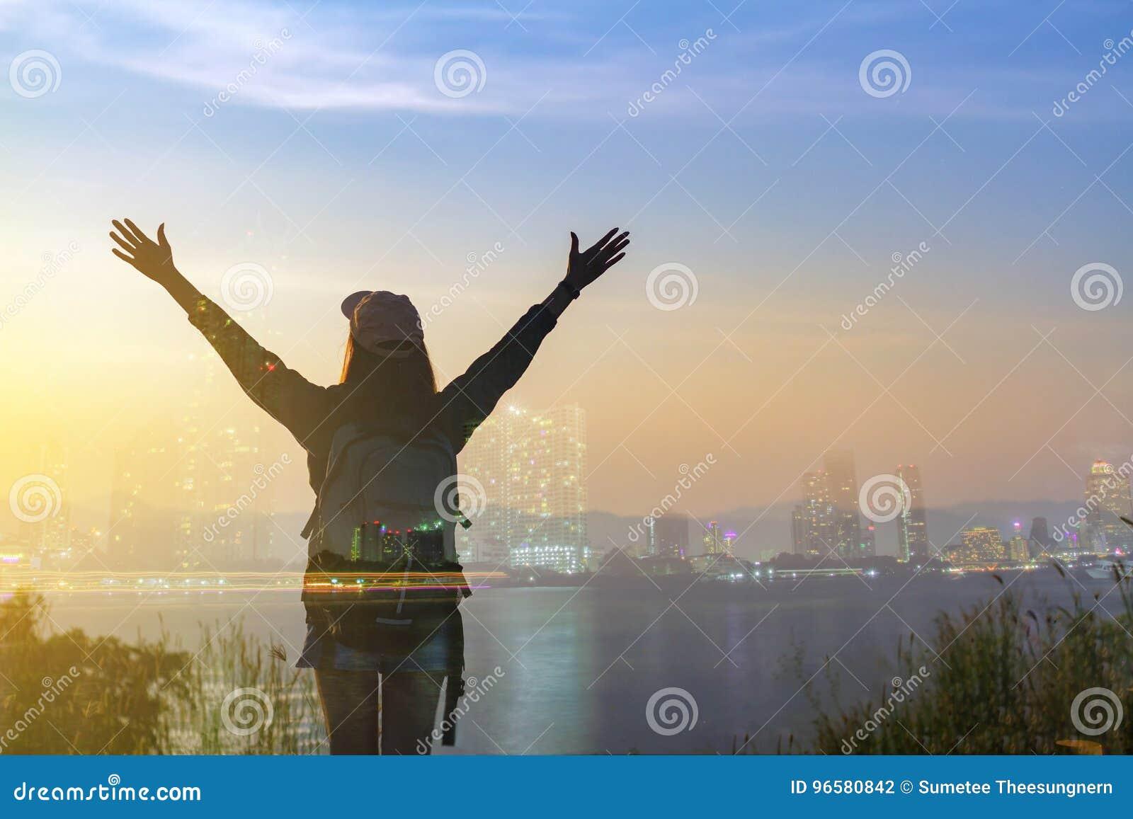 Mulher do viajante da liberdade da exposição dobro que está com braços aumentados e que aprecia uma natureza bonita e que cheerin