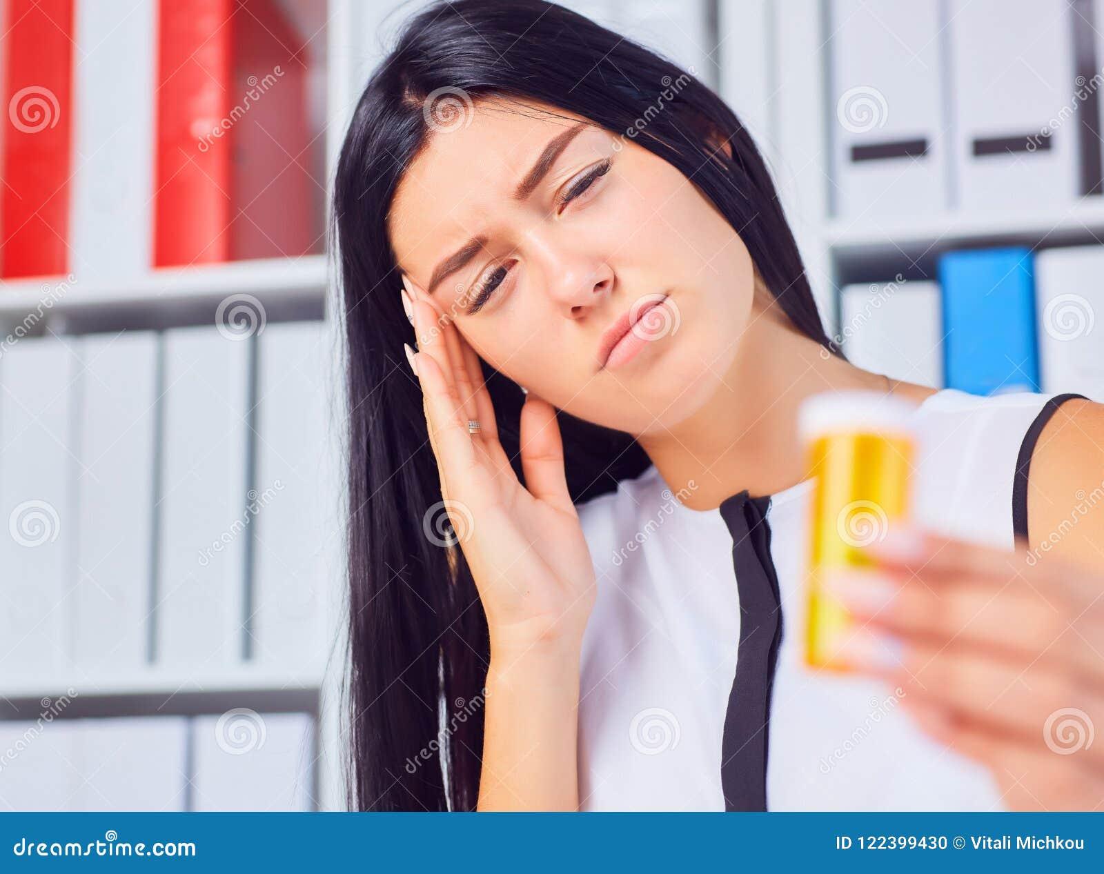 Mulher doente cansado bonita nova que senta-se no local de trabalho no escritório que guarda a garrafa com comprimidos Sentimento