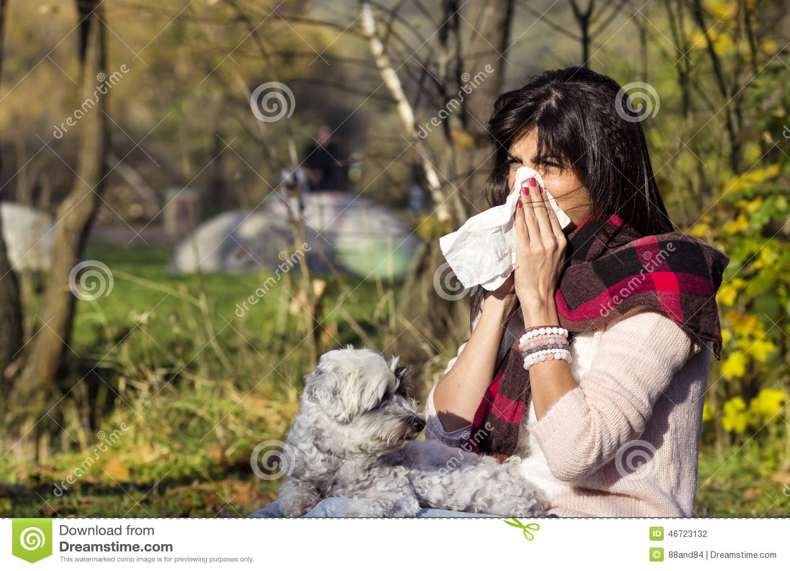 Mulher doente que relaxa no parque do outono com seu cão