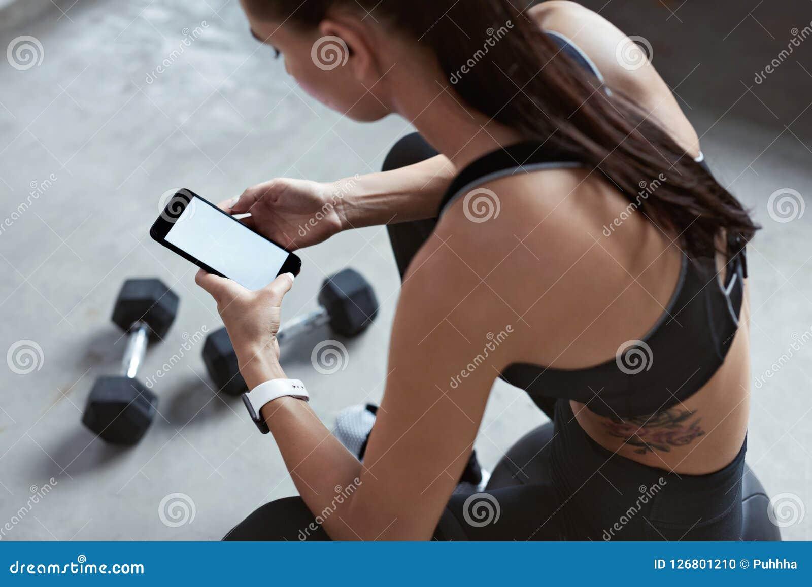 Mulher dos esportes no Sportswear da forma usando o telefone no treinamento