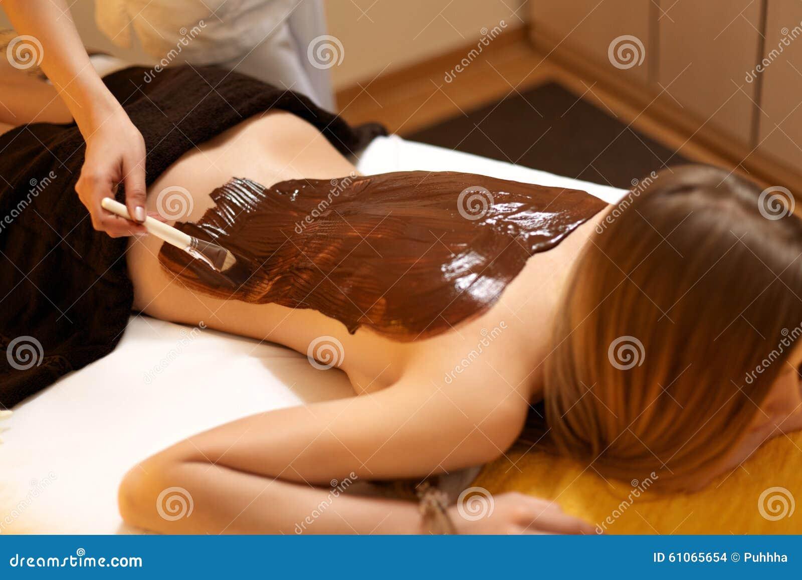 Mulher dos termas A jovem mulher obtém a máscara do corpo do chocolate no salão de beleza