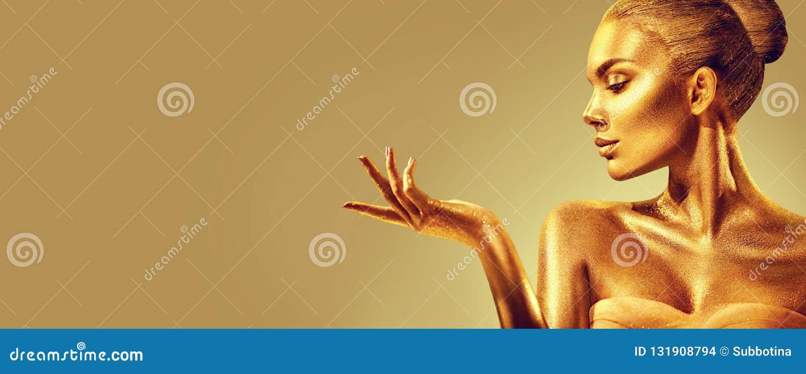 Mulher dourada Menina do modelo de forma da beleza com pele dourada, composição, cabelo e joia no fundo do ouro