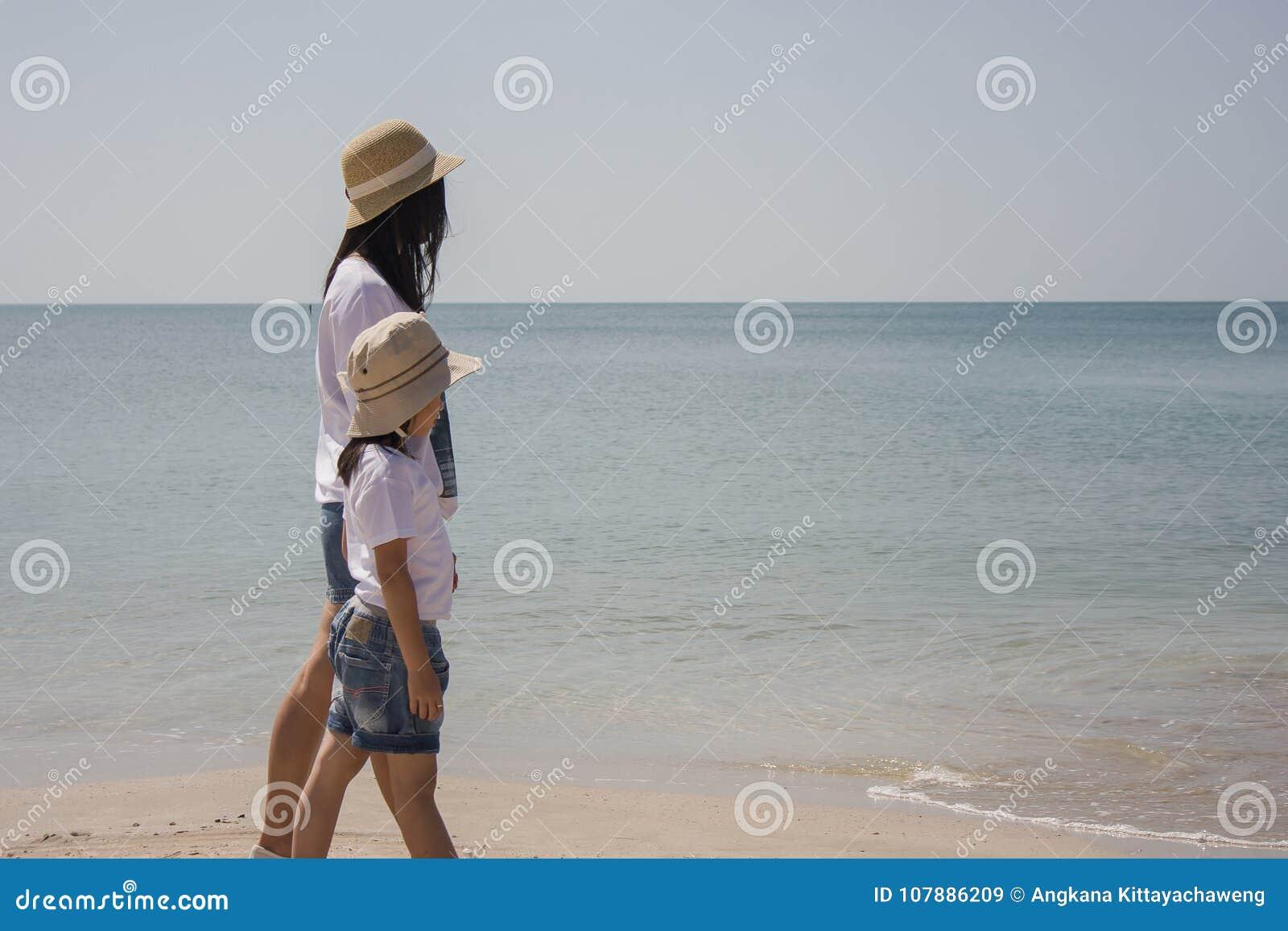 A mulher e a criança que andam na praia da areia e que sentem relaxam com opinião do seascape no fundo