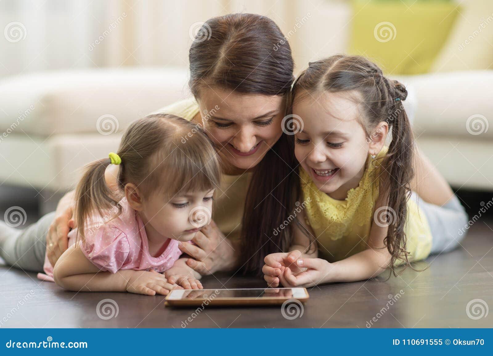 Mulher e crianças felizes que usam a tabuleta digital no assoalho em casa